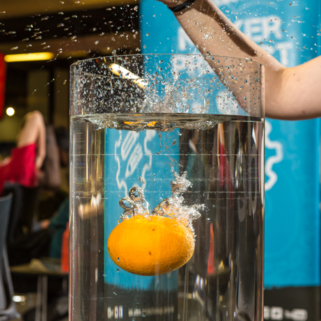 Orange being dropped into a tank of water