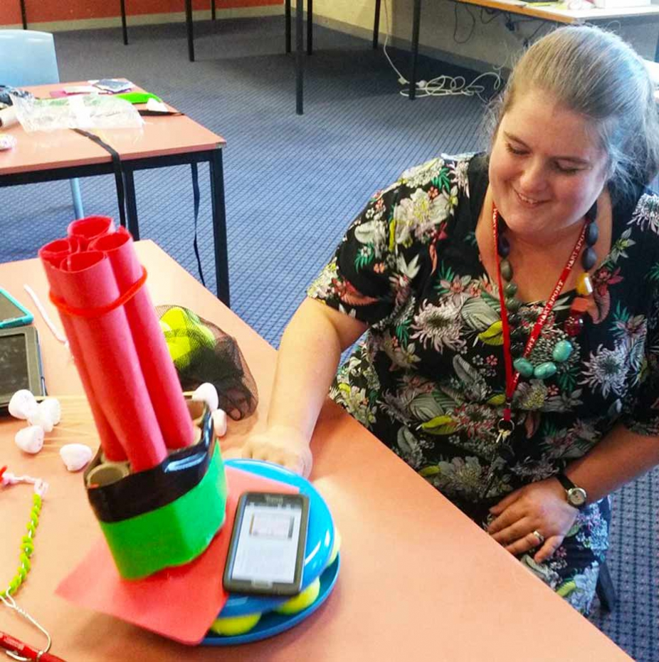 teacher measures vibration in a shaking structure made of cardboard with a smart phone.
