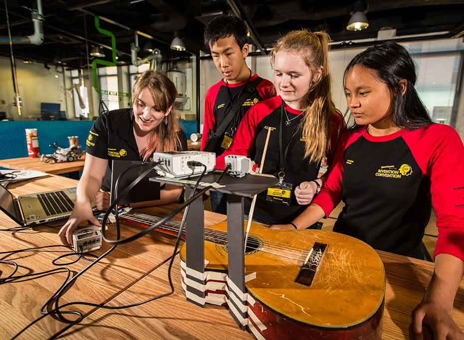 Four people looking at a robotic guitar