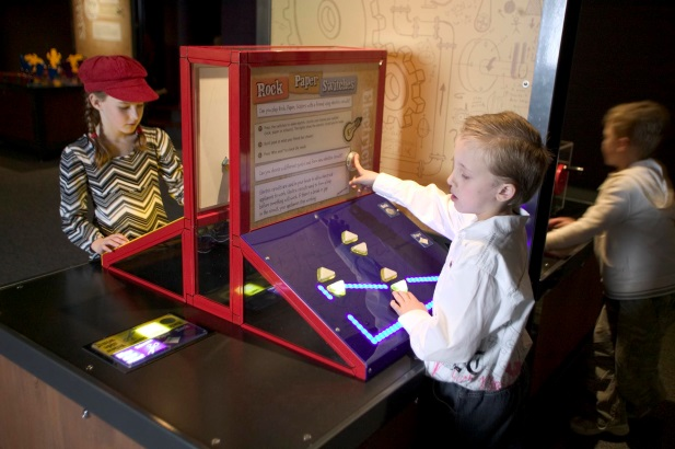 Two kids looking at a display on a table