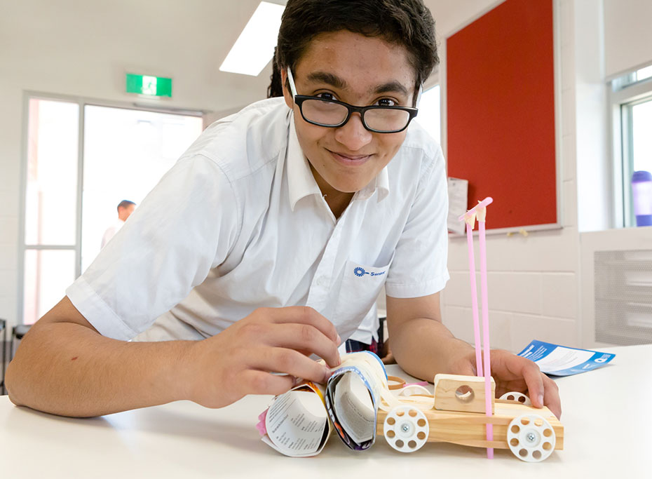 A student building a model car with a crumple zone