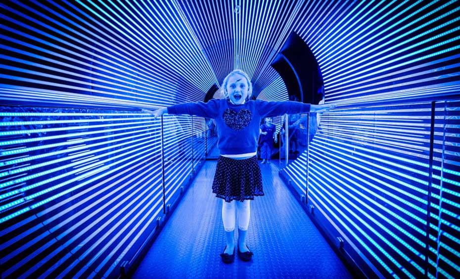 A girl stands in the Rototron, a tunnel made up of blue lights.