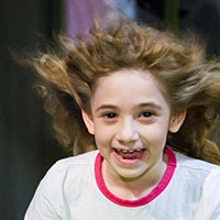 A young girl smiling with her long hair being blown backwards.