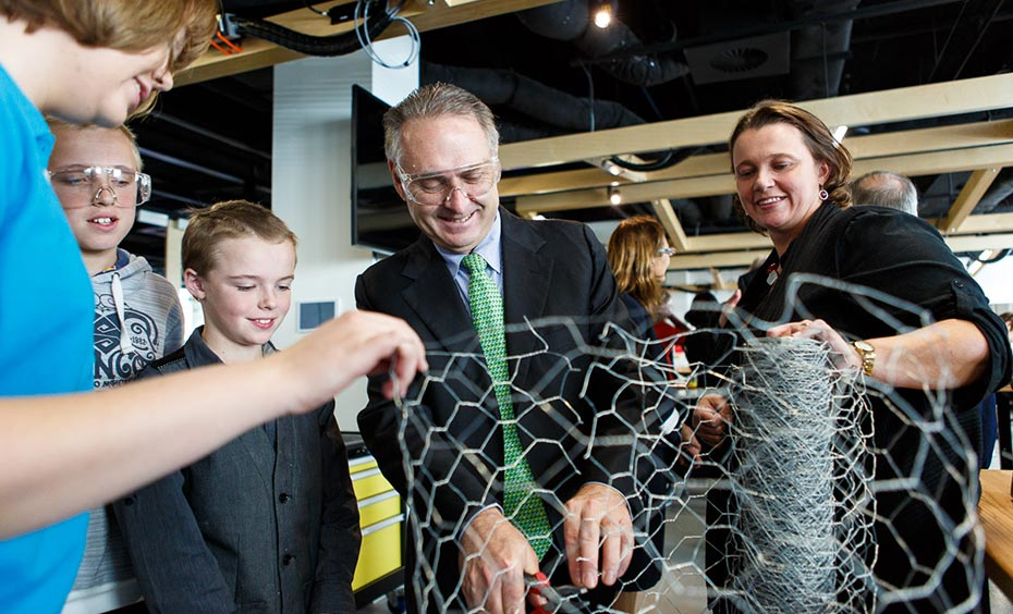 A man, two woman and two school children working with chickenwire.