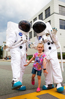 Two astronauts and a young child outside Questacon