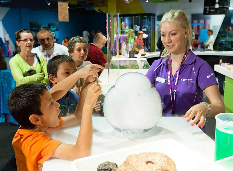 Primary school children interacting in a science experiment with Questacon presenter in the Q Lab at Questacon Parkes