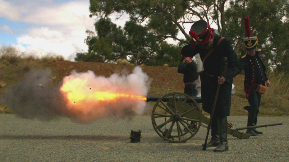 Three men in historical black military uniforms are firing a small cannon outside.
