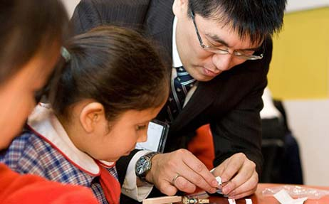 A man wearing glasses and wearing a suit, is watch by two small school girls as they construct something on a table.