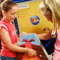 two young girls interacting with a science exhibition