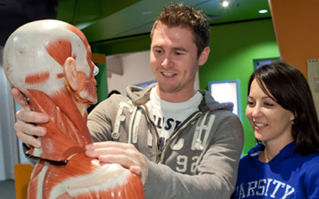 A man a woman smiling, wearing track suit tops are looking and handling a model human skeleton with muscles on it.