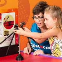 A young girl plaing with a science exhibit while a young woman looks on