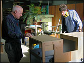 two men fabricating a timber exhibit