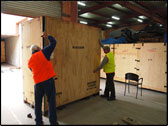 Two men with safety vests, putting in place a side to a large plywood box.