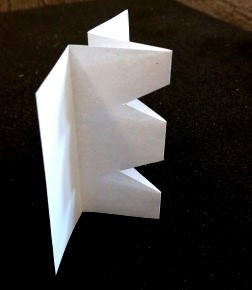 An image of folded paper showing two v-shaped sections removed