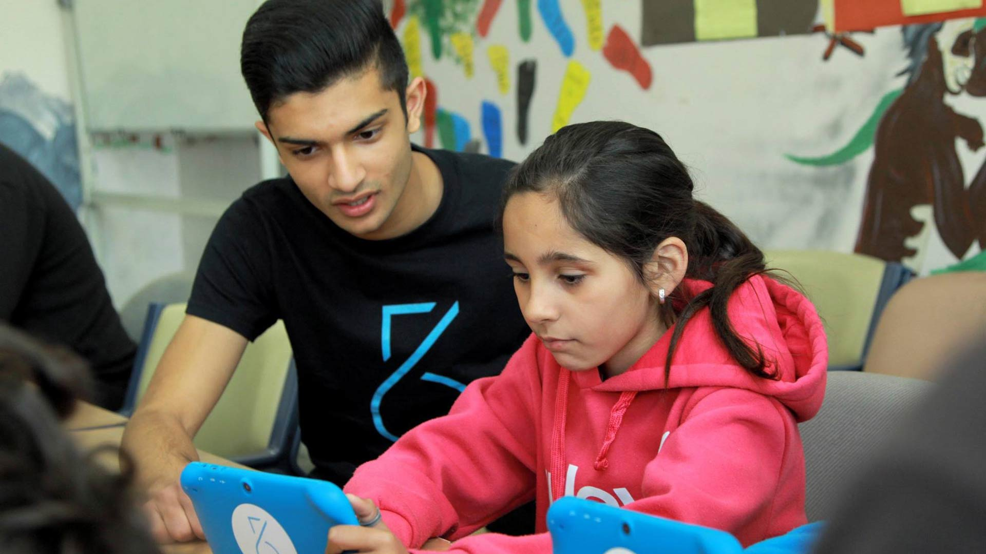 Taj Pabari and a young girl work on a Fiftysix Creations tablet
