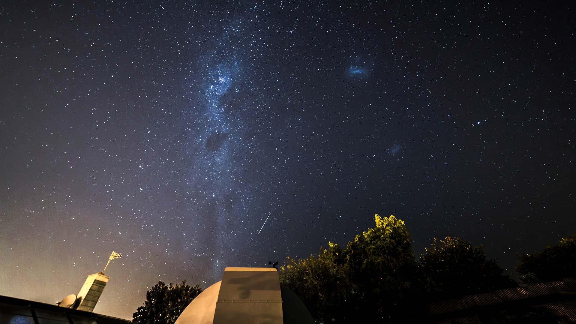 A large telescope pointed at the night sky and the milky way with a shooting star.