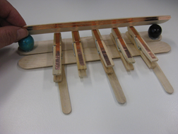 Title: Peg piano - Description: A large popstick is placed on top of a series of five pegs affixed to another large popstick