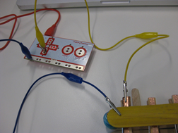 Title: Connecting the peg piano - Description: A small circuit board is connected by crocodile clips to a peg covered in copper tape.
