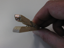 Title: Copper tape peg - Description: A wooden peg with copper tape on one side is being squeezed by a hand.
