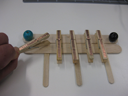 Title: Making the peg piano - Description: Five pegs with copper tape are stuck onto a pair of large popsticks