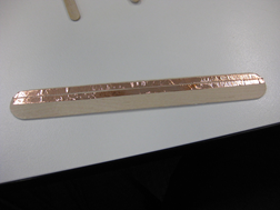 Title: Large popstick - Description: A large popstick is half covered with two strips of copper tape