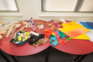 Title: Photo of table with building materials - Description: Two round tables covered in a variety of recycled materials such as balls, wooden pieces, stockings, rubber bands, ballons and cardboard folders.