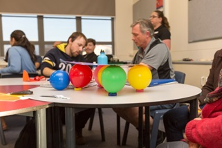 Title: Photos of a shake table - Description: A cardboard folder placed on four ballons balanced on milk bottle lids to create a shake table. Teachers working together in background.