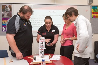 Title: Teachers receive instructions - Description: Three teachers are looking at a presenter who is demonstrating the use of a Samsung mobile phone. A tower made of postcards balanced on a coreflute platform is in the foreground.
