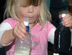 A young girls holding two plastic bottles: one clear and containing rice, and one opaque and covered in black tape.