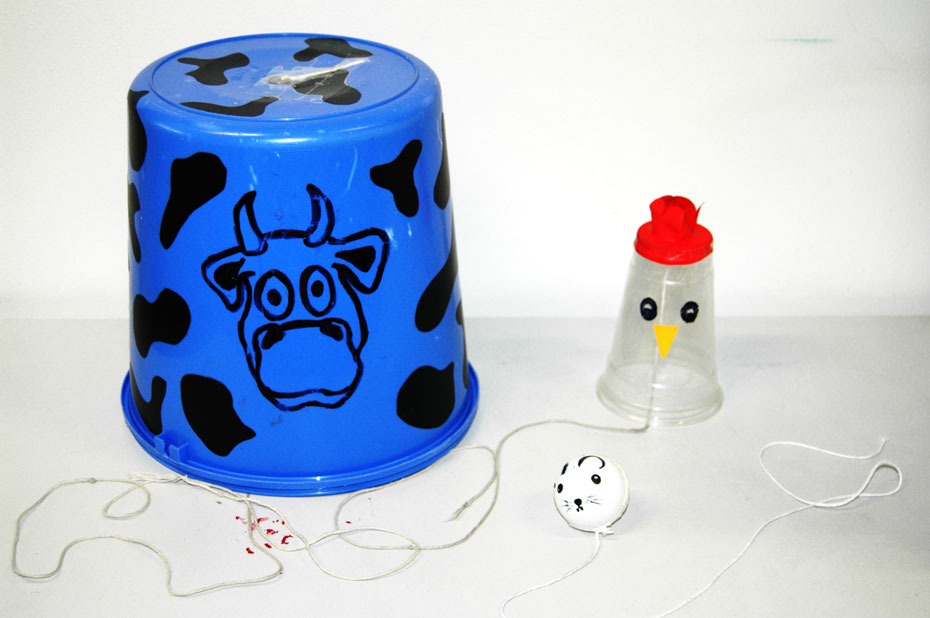 A blue bucket with a cow face painted on, a small plastic cup decorated to look like a chicken, and a white ping pong ball decorated to look like a mouse. Each object has string attached.