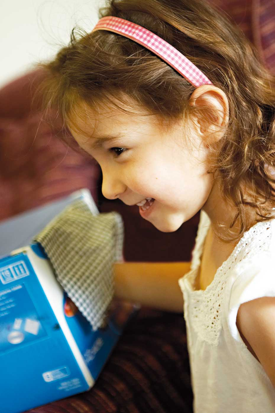 A young girl smiling with her right hand reaching inside a blue cardboard box that has a teatowel covering a hole in the side of the box.
