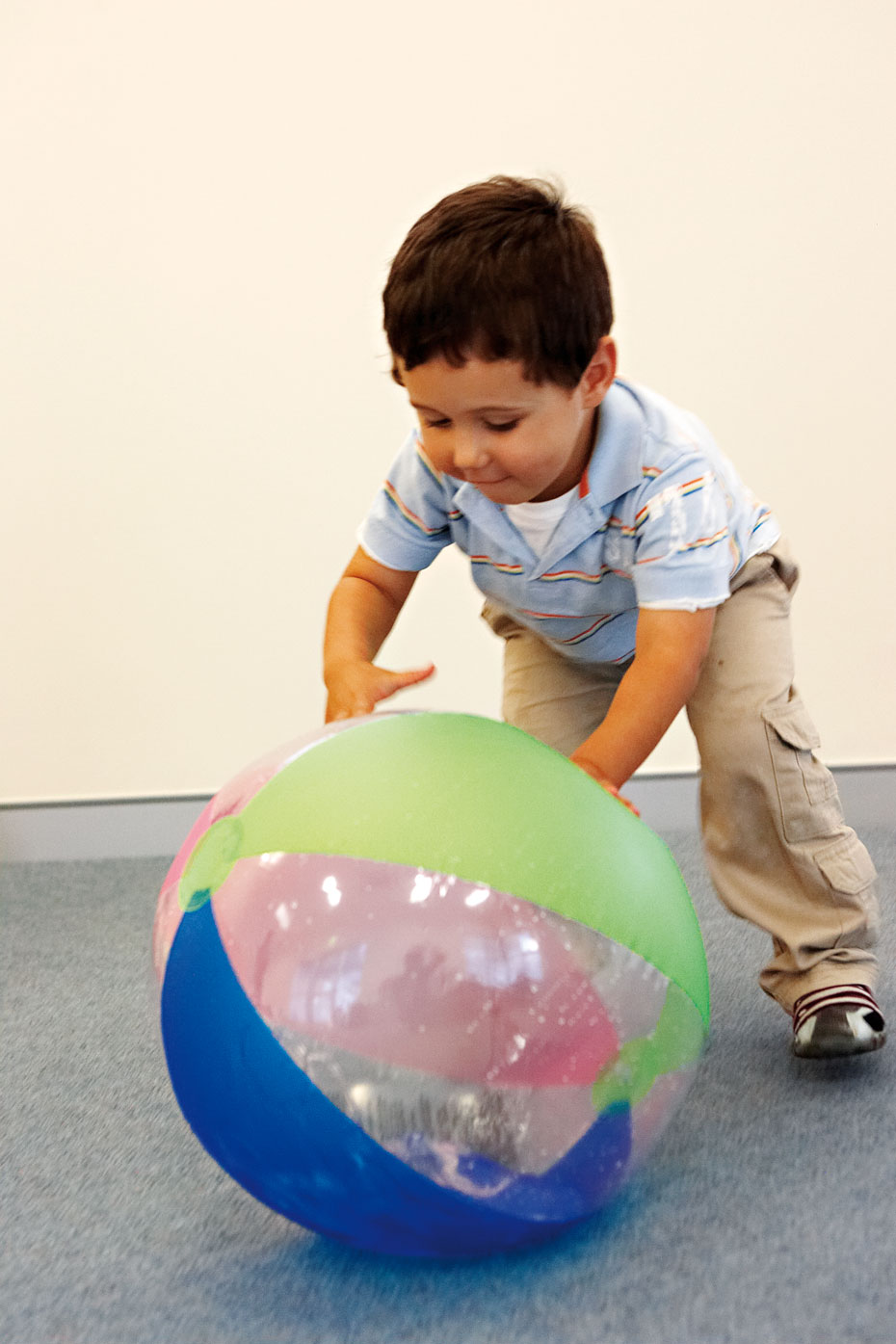 A young boy standing over and reaching out for a rainbow beach ball.