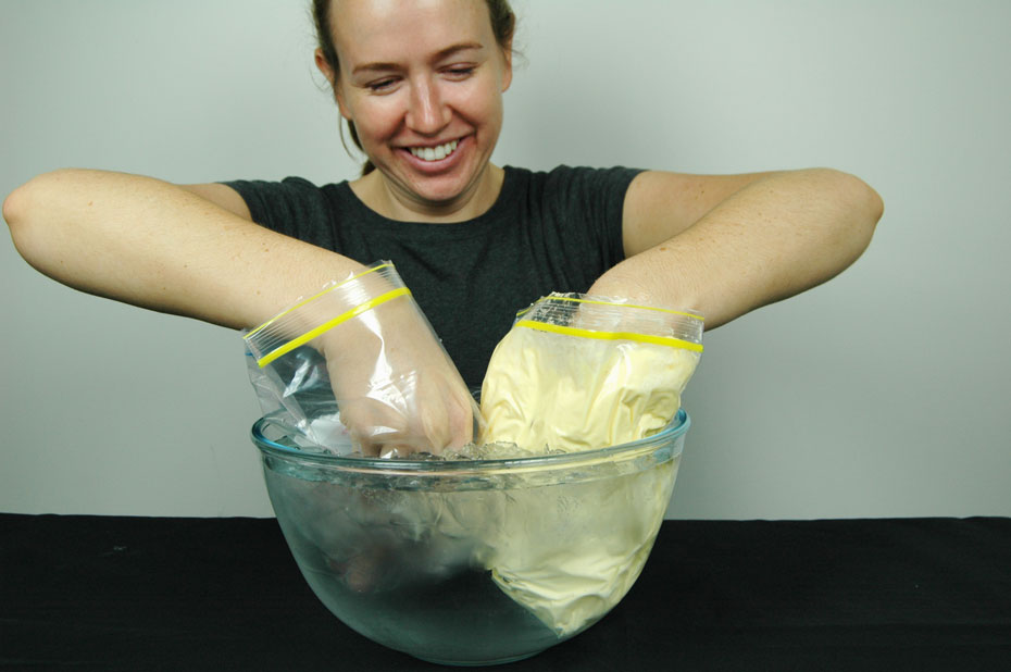 A female Science Squad presenter holding her hands inside two separate plastic bags. The bags are sitting in a bowl of ice water.