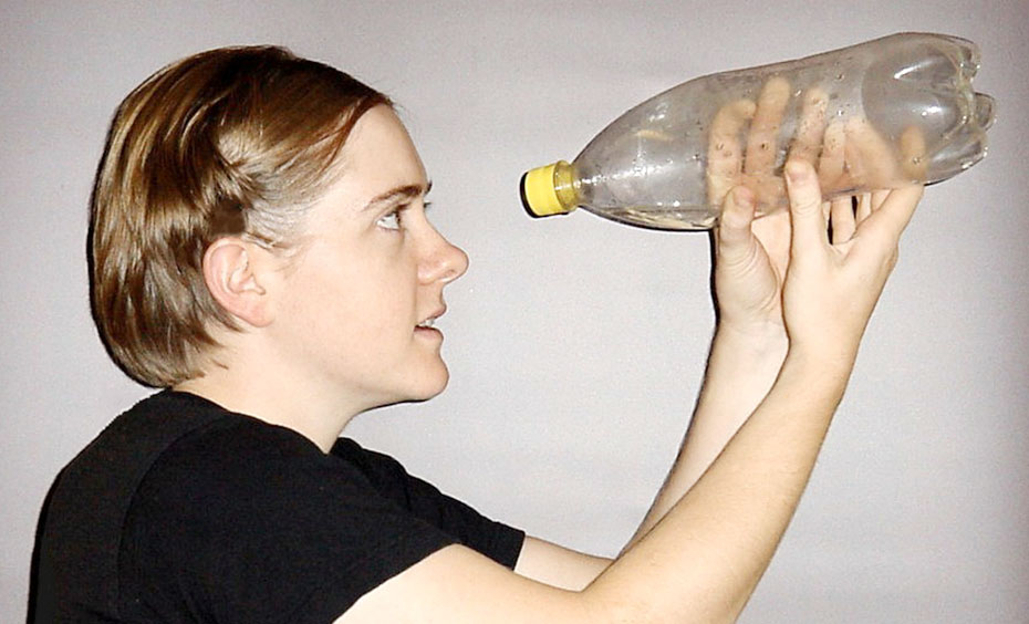 A young woman hold up to her face an empty clear plastic 1.25 litre bottle