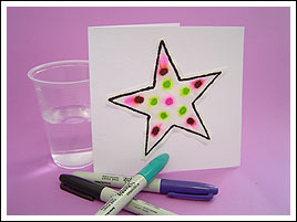 A white card standing upright with a pink-and-green spotted star on the front. A plastic cup is sitting next to the card, and three coloured markers are sitting in front.