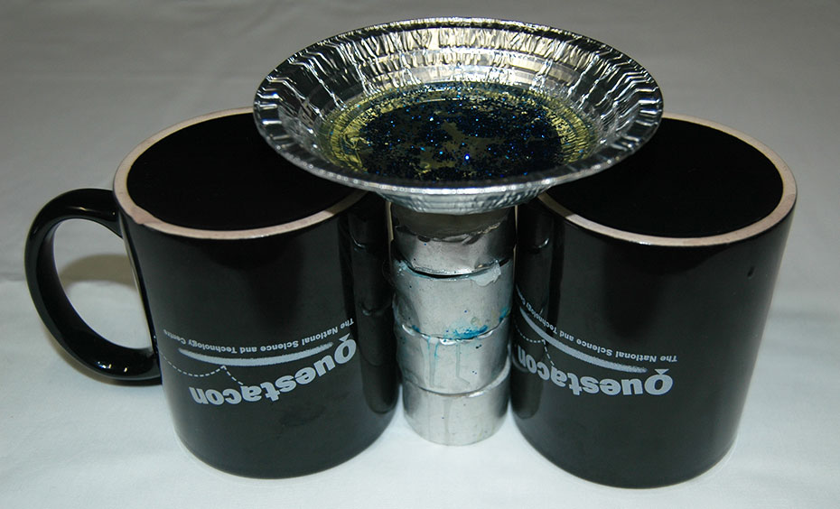 two black upside down mugs on a white table cloth, with a silver cylinder between them, and a small aluminium dish sitting on the cylinder