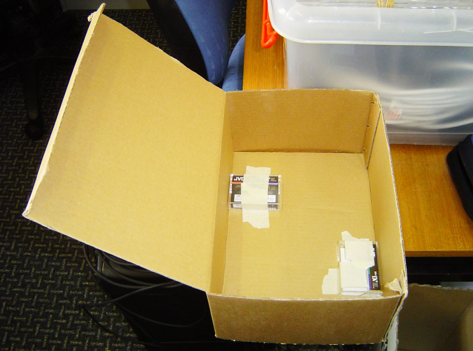 A open cardboard box with two cassette tapes taped with masking tape to the bottom of