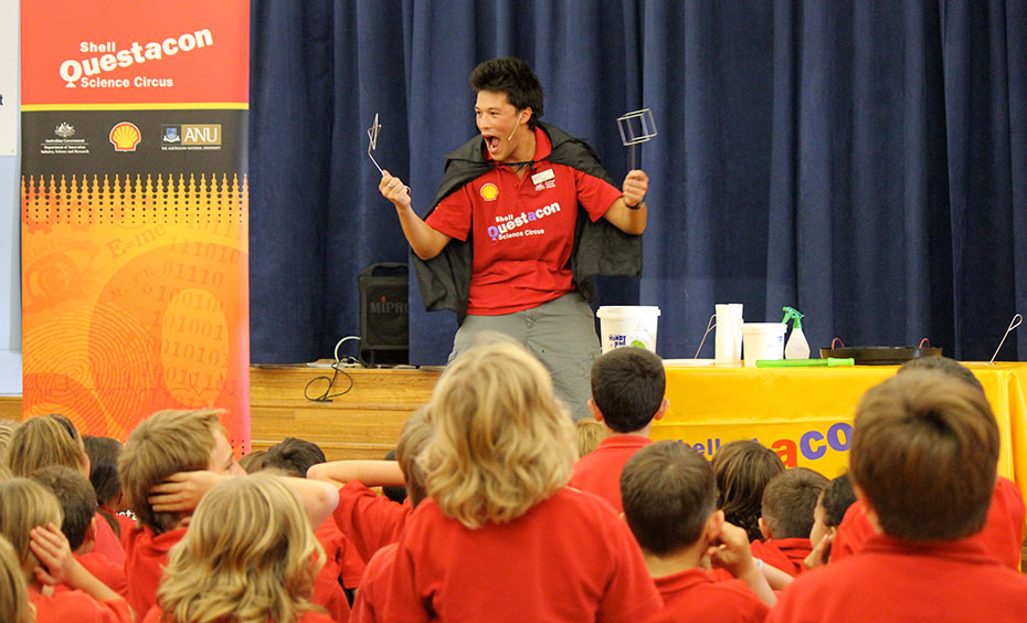 A man wearing a red polo shirt with Shell Questacon Science Circus on the front, is wearing a black cape and performing in front of a group of primary school children all sitting and wearing red polo shirts. To the left is a red, black and orange pull up banner with sponsors printed on it, and behind the man is a yellow table with a variety of house hold objects on it.