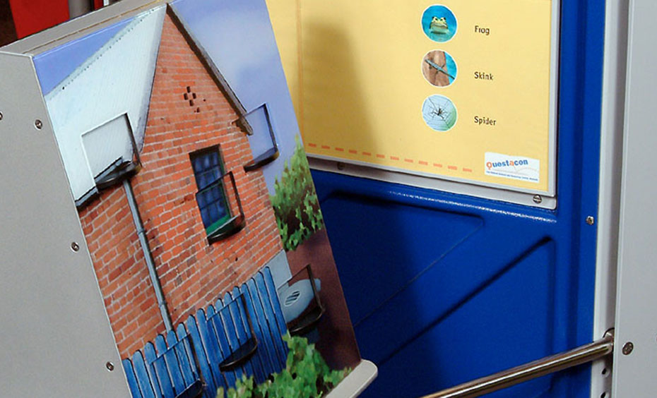 An exhibit with a yellow and blue information panel at the back and a triangular prism with a picture of house at the front.