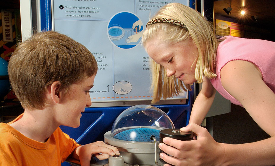 A boy and girl operating a button and watching a clear dome with weights attached. In the background is a blue and white information panel.