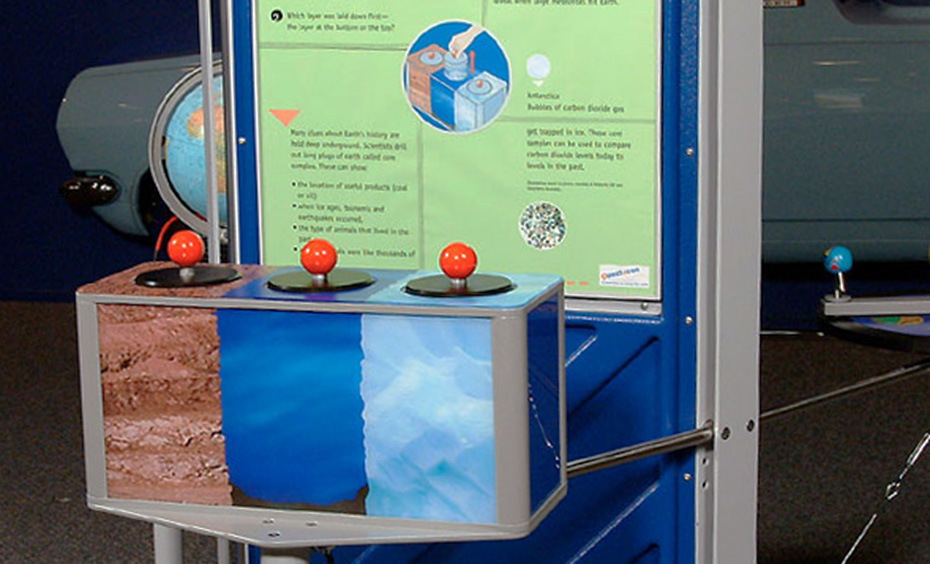 A blue, green and grey exhibt which has 3 core sample boxes at the front with red knobs on top of each, and a large vertical information panel at the back.