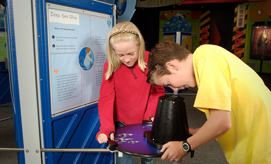 A girl watches on as a boy looks down and through a black tube eyepiece sitting on a purple round table. To the left is a blue information panel.