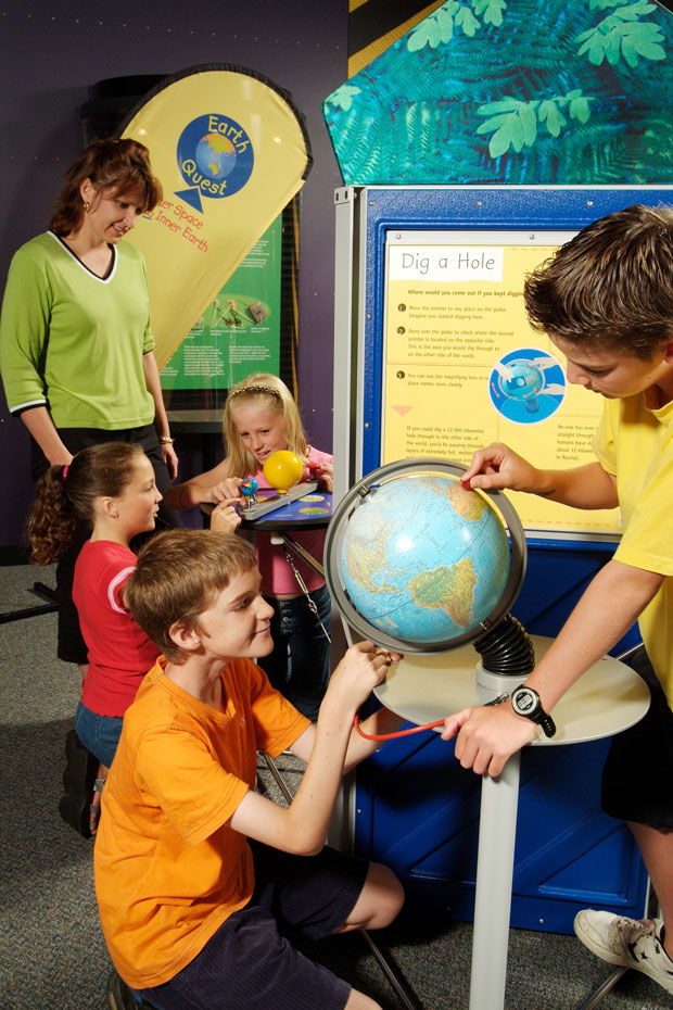 4 children and a woman looking at two separate exhibits which show models of the earth and sun.