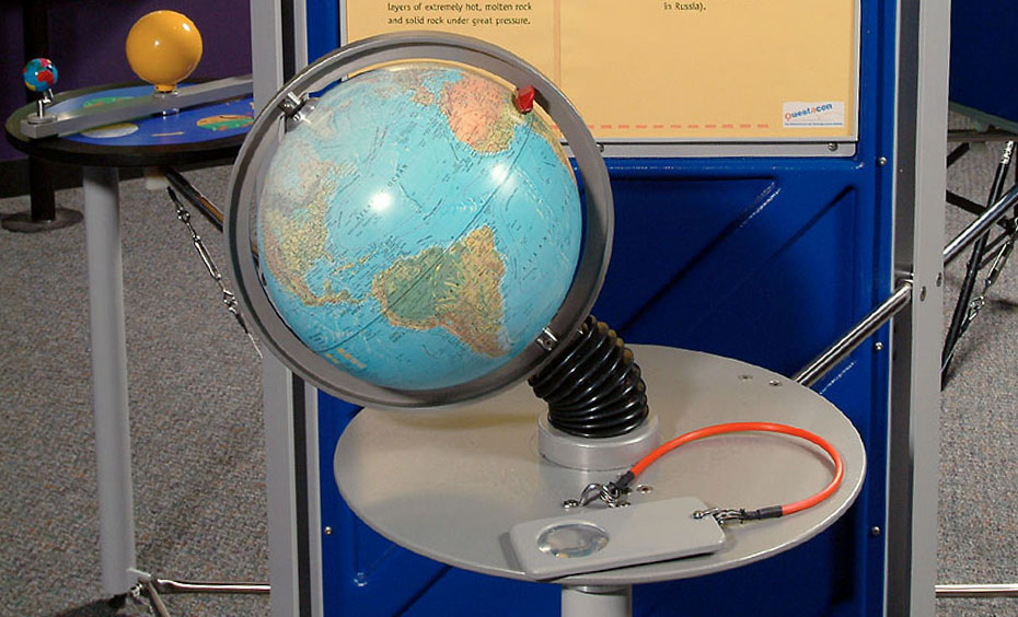 A model globe in front of a blue and yellow information panel.