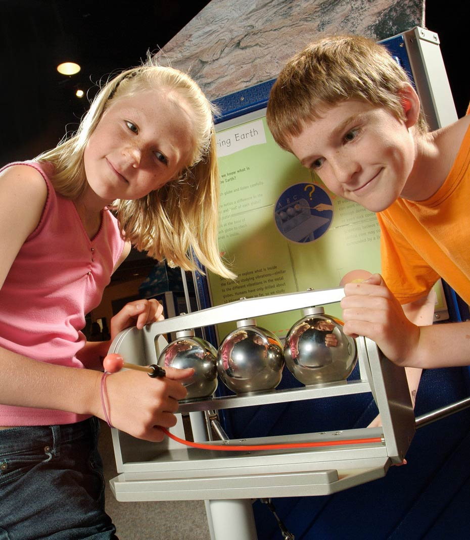A boy and girl standing in front of a green and blue vertical information panel have their hands on a grey framed exhibit, which has 3 chrome spheres. The girl has a small mallet.