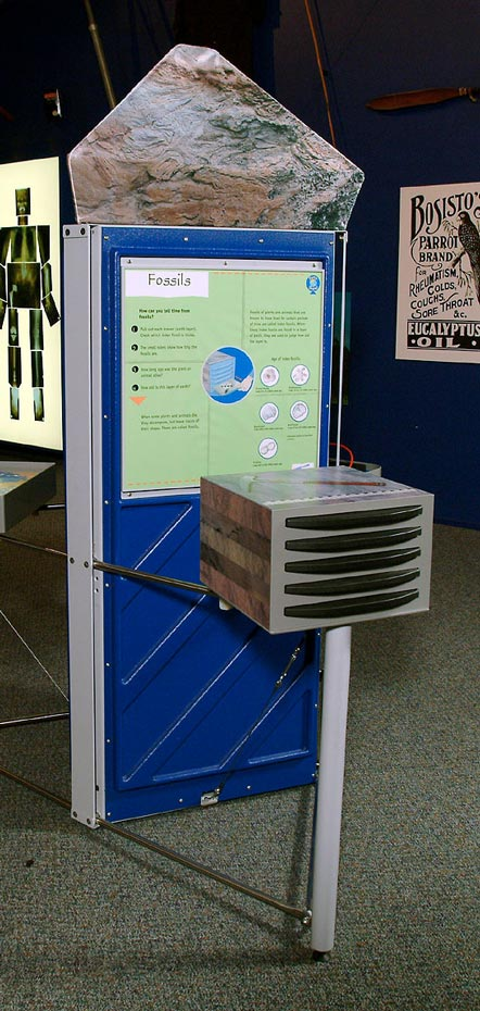 A blue, green and grey exhibit, with draws at the front and an information panel at the rear.