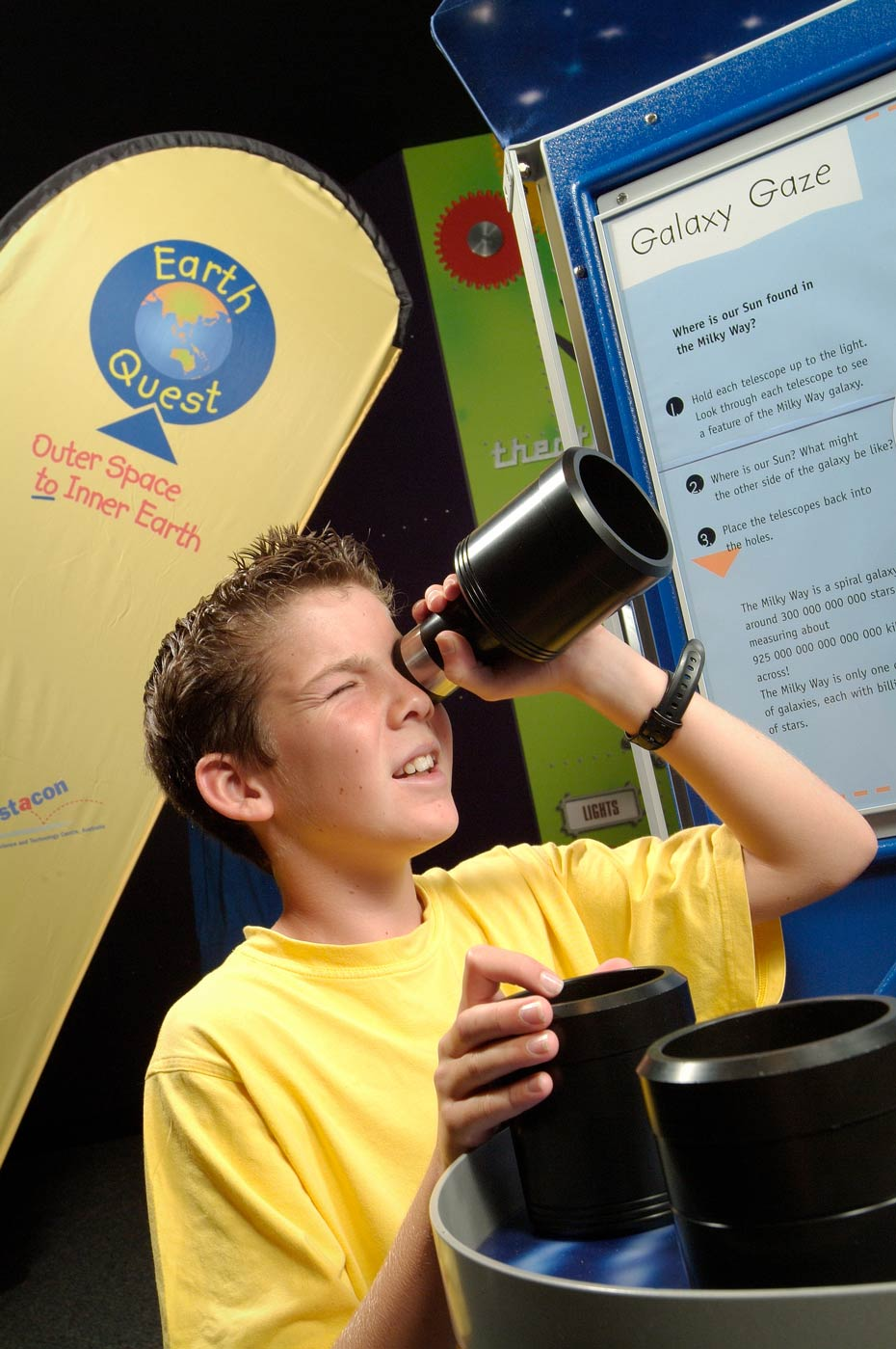 A boy in a yellow t-shirt holding up a black telescope to his eye. In the background are yellow, green and blue information panels.