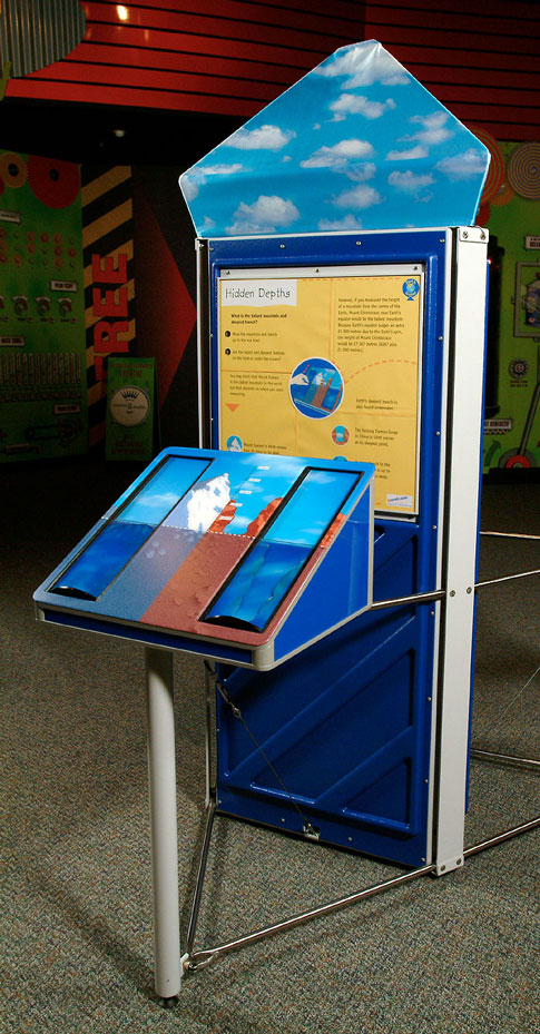 A yellow, blue and brown exhibit that has a triangular prism at the front and a large veritical information panel at the back.