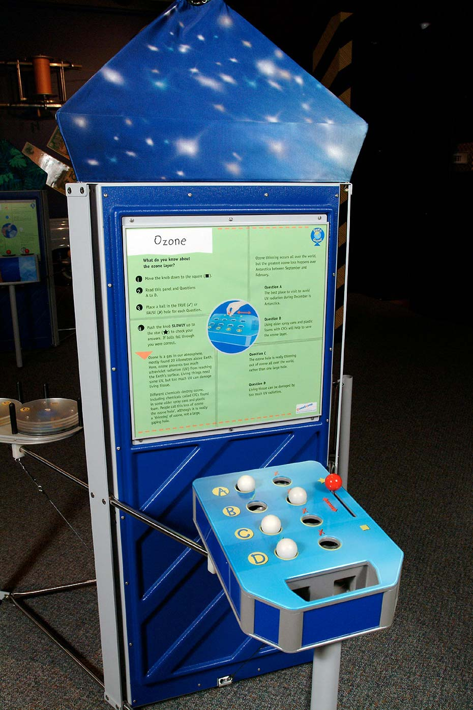 A blue and green exhibiti with a vertical information panel at the back and a horizontal table with white balls, a red lever and the letters 'A', 'B', 'C' and 'D' displayed.