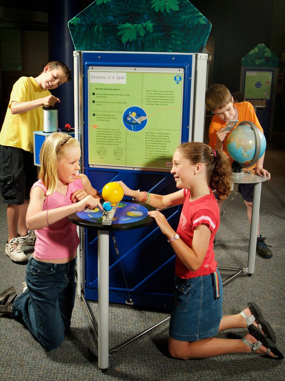Two girls kneeling in front of a blue and green table and information panel. On the table is a yellow model sun and blue earth. In the background are two boys looking at other nearby exhibits.